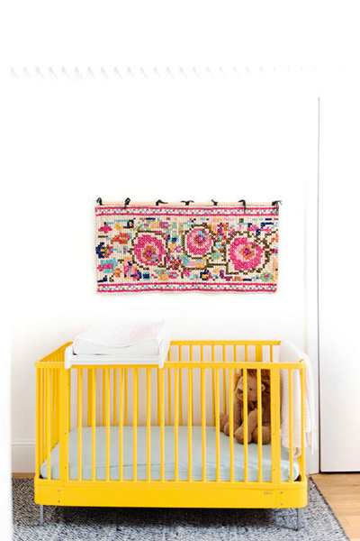 yellow cot with rug on wall