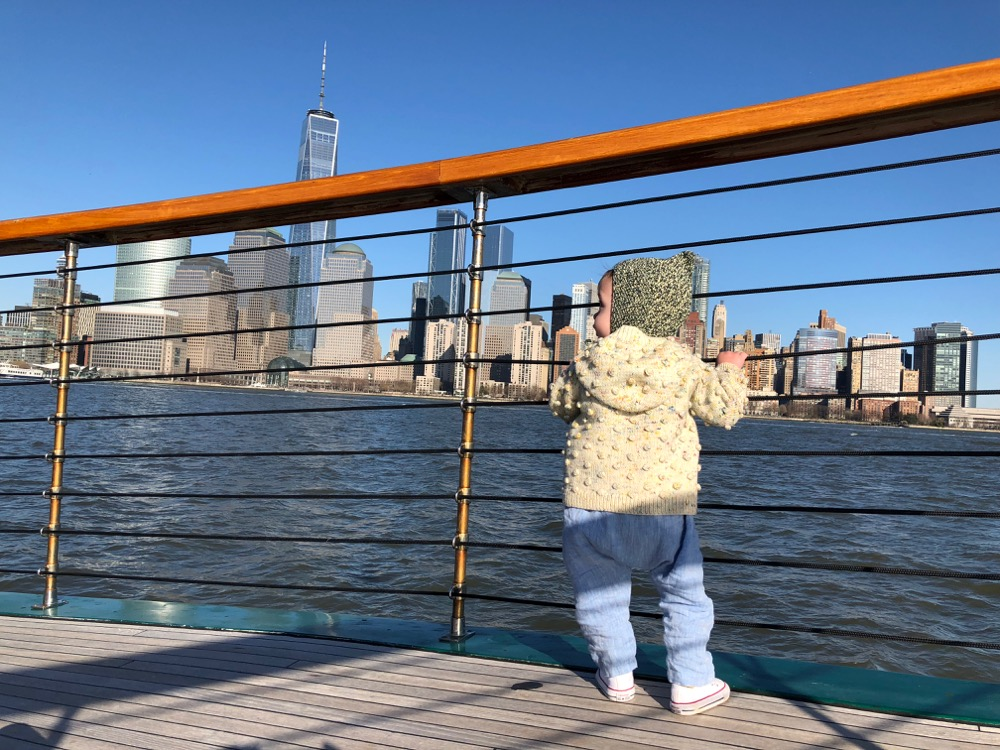Child on the deck of the boat Manhattan II looking at the New York City skyline