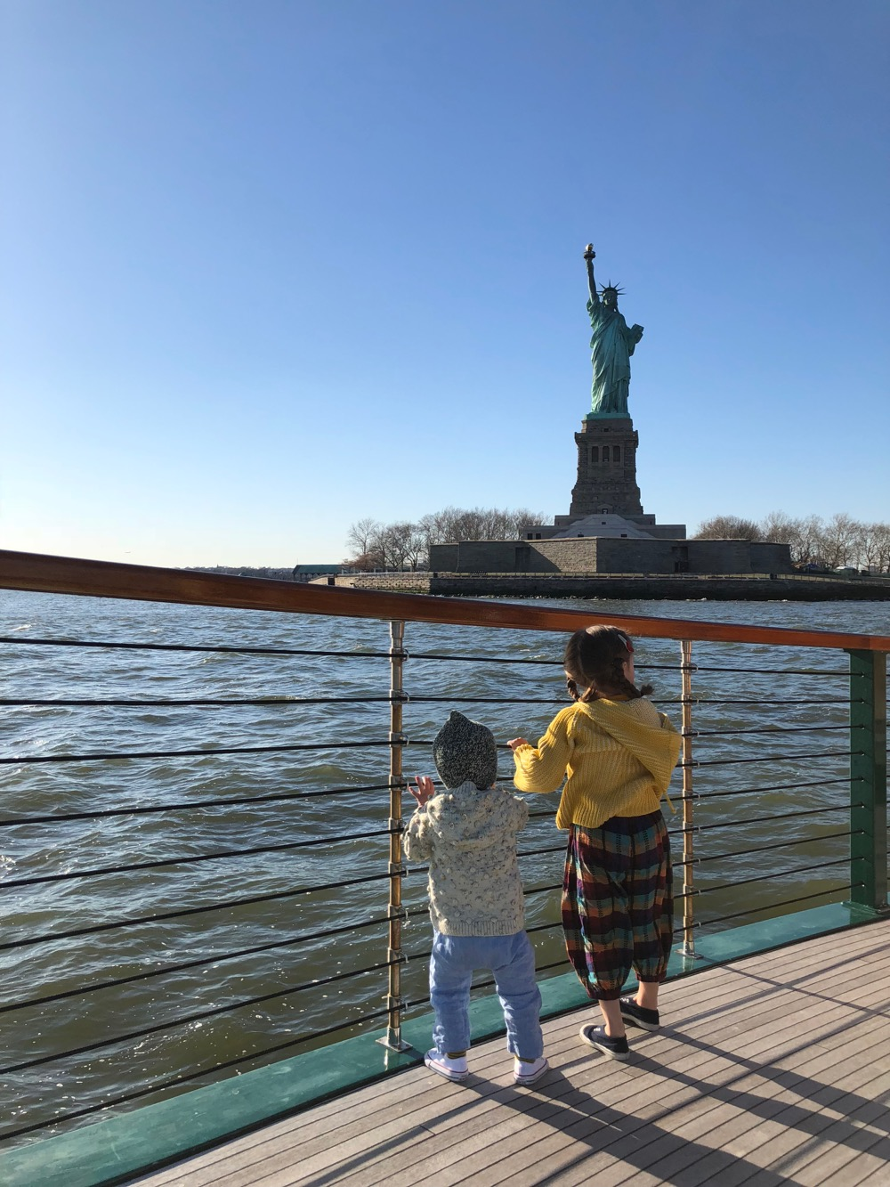 Two children on the deck of the boat looking at the Statue of Liberty