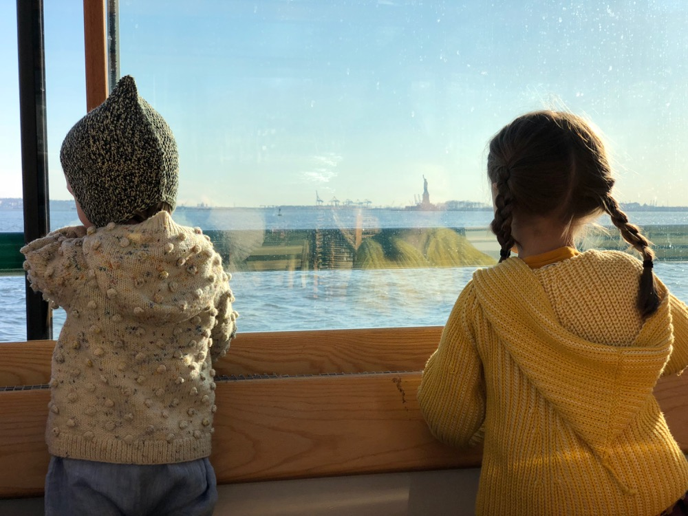 Two children look at the window of a boat toward the Statue of Liberty