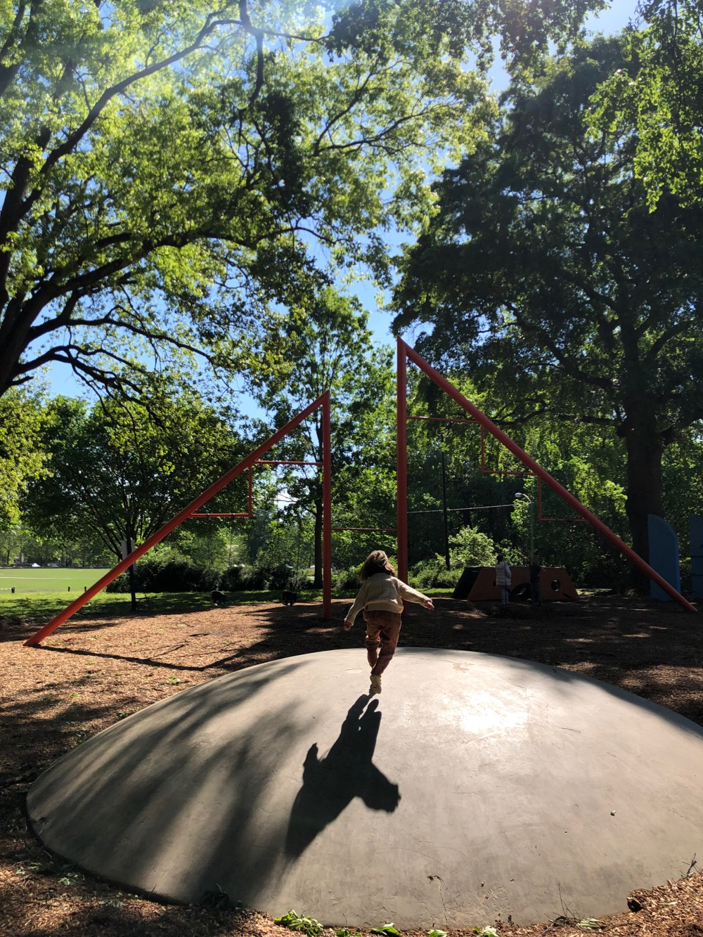 Child running across the domed form at Noguchi's Playscapes