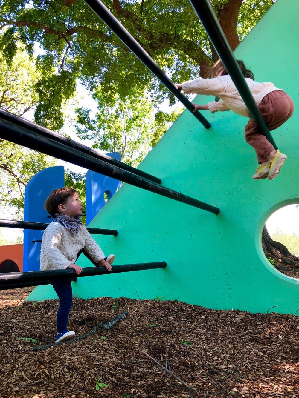 Two children climbing on the green structure at Noguchi's Playscapes