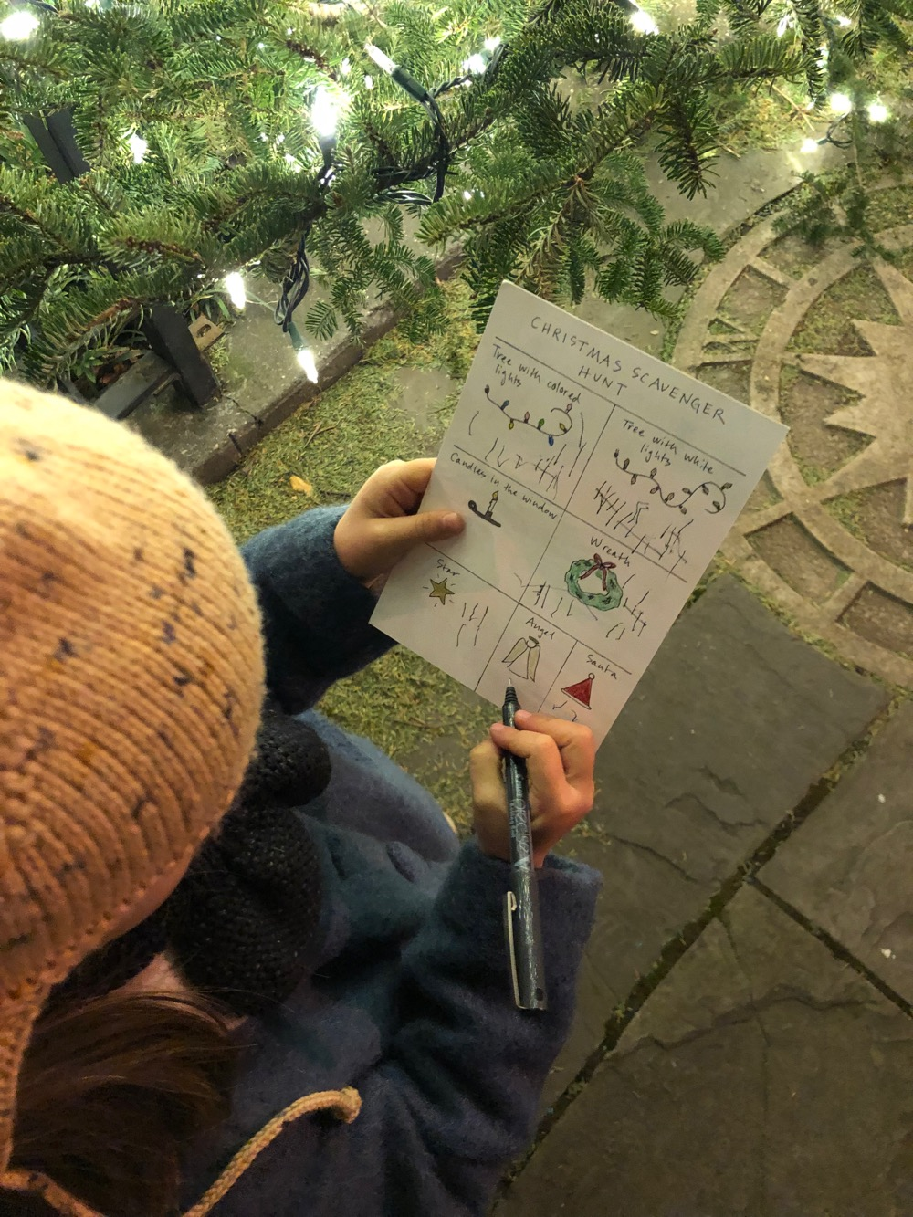child filling out a scavenger hunt score card